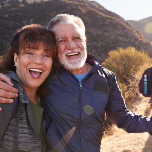 Portrait Of Smiling Senior Friends Hiking In Along Base walk at Uluru